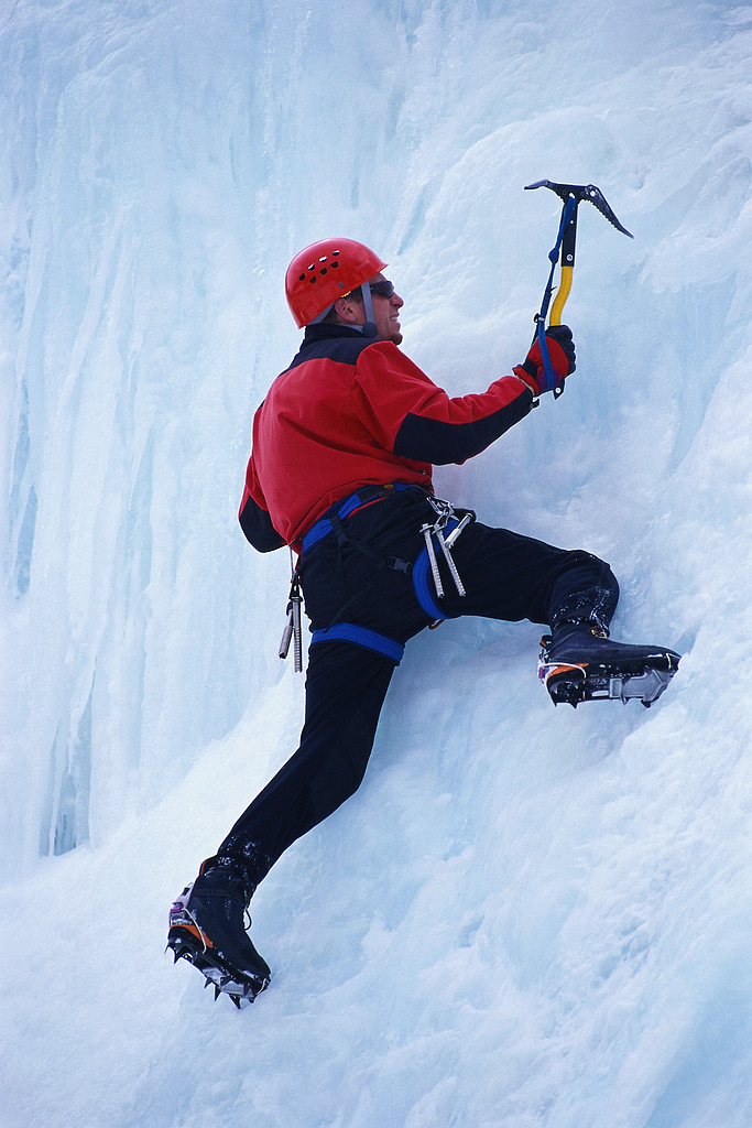 Moutain climber scaling a wall of ice